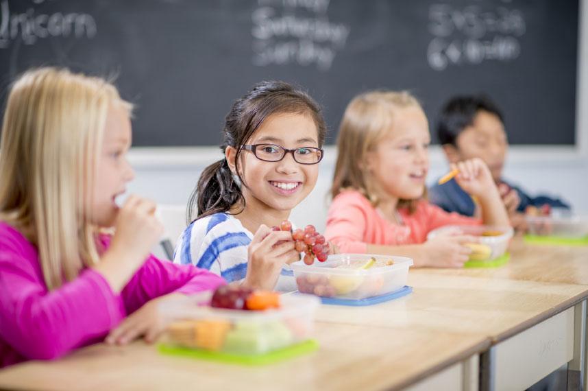 Three children eating a school lunch