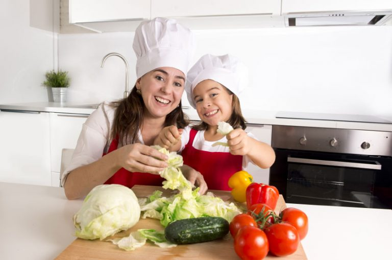 Mother and daughter in white hats behind a pile of vegetables