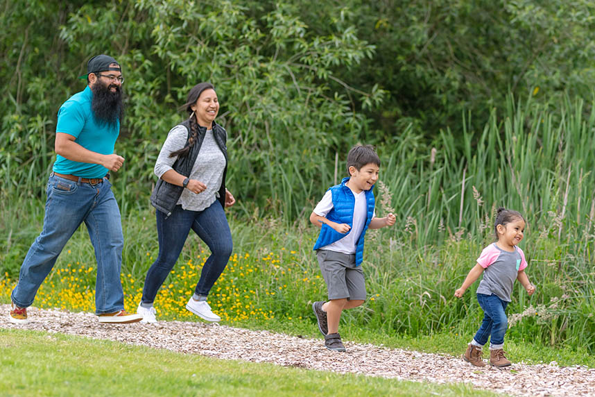 Two young kids and their parents walking out in nature