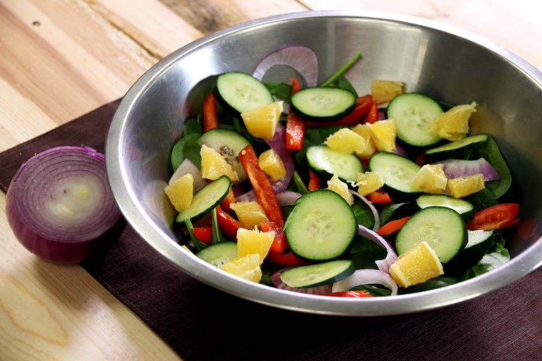 metal bowl with spinach salad and other vegetables