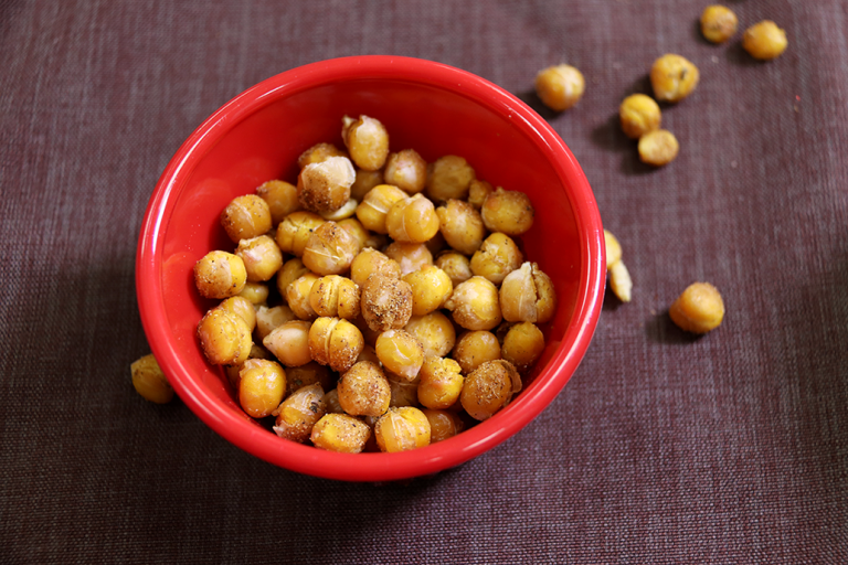 roasted chickpeas spilling out of a red bowl onto a brown background
