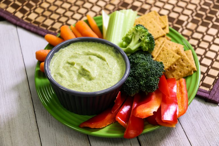 Broccomole dip on a plate with vegetables