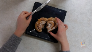 a round, iced cinnamon roll sits on a plate; sliced in half by two hands holding a knife