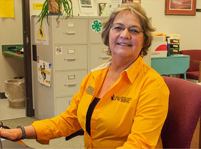 Janet Benson sitting at desk.