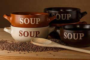 Soups bowls with lentils and a wooden spoon