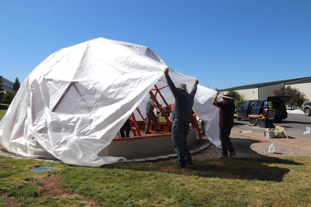 People pulling a large sheet of plastic over a wooden done structure to create a geodome.