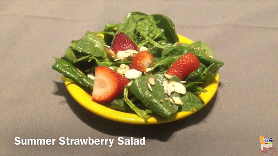 """Prepared salad on yellow plate resting on brown background with white text """"Summer Strawberry Salad"""""""