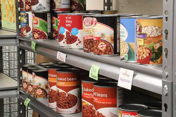 Cans of various beans on a grey metal shelf with signs below reading 'beans', 'chili beans', and 'vegetarian'.