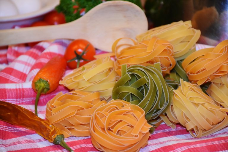 colored pasta next to whole red peppers