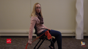 A seated woman stretches a red band behind her back