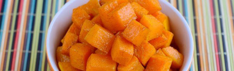 Orange bowl of diced sweet potatoes sprinkled with cinnamon,