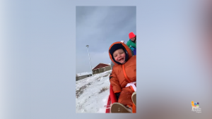 young boy in orange snowsuit on sled
