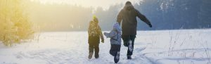 An adult and two kids run down a snowy road