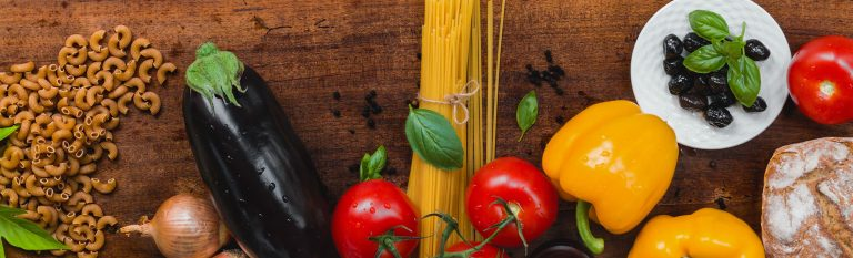 Pasta, eggplant, peppers, olives, and bread on a wooden background