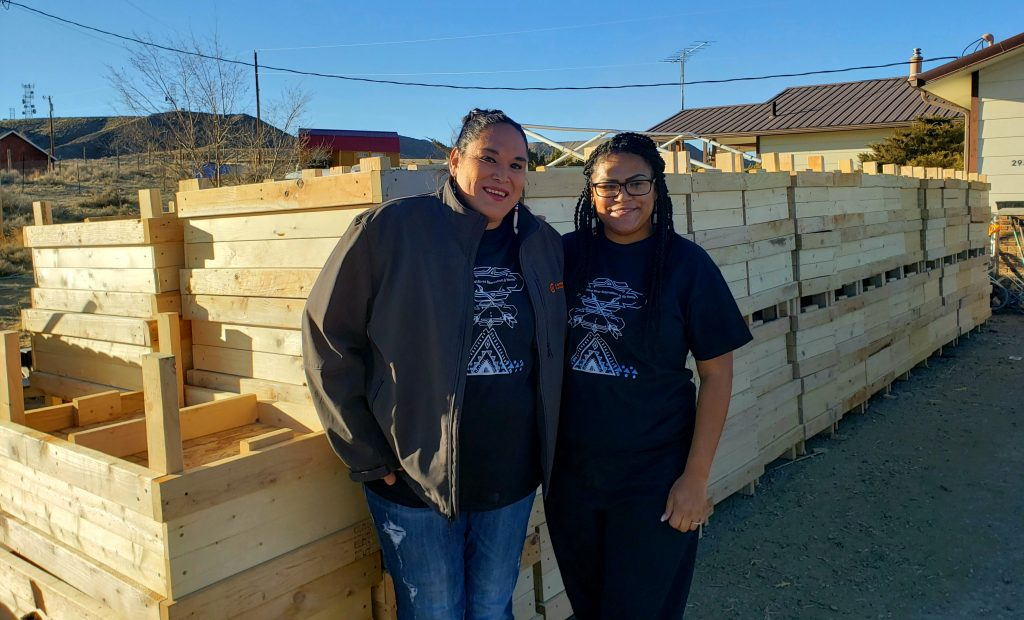 Darrah and Deneica in front of wooden garden boxes
