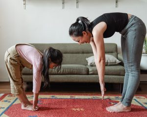 a woman and young girl stretch in front of a couch